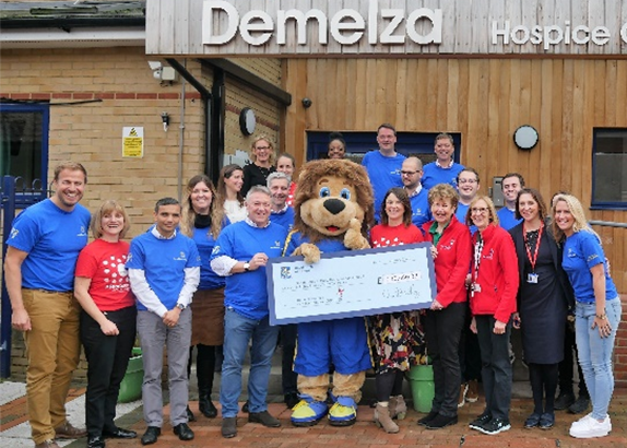 Demelza's staff receive a cheque from Team RBC